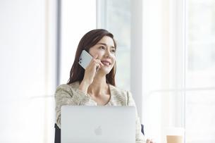スマートフォンを持つ働く女性の写真素材 [FYI04538384]