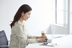 働く女性とノートパソコンの写真素材 [FYI04538390]