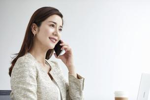 スマートフォンを持つ働く女性の写真素材 [FYI04538394]