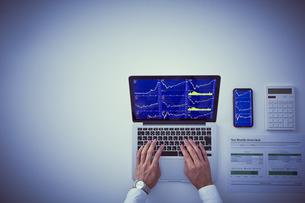 株のチャートを映したパソコンとスマートフォンと男性の手元の写真素材 [FYI04539370]