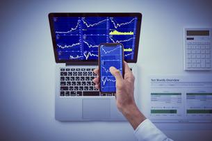 株のチャートを映したパソコンとスマートフォンと男性の手元の写真素材 [FYI04539371]