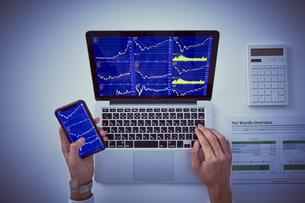 株のチャートを映したパソコンとスマートフォンと男性の手元の写真素材 [FYI04539372]