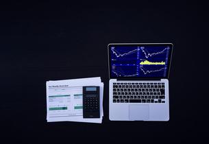 株のチャートを映したパソコンと資料と電卓の写真素材 [FYI04539377]