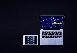 株のチャートを映したパソコンとタブレットの写真素材 [FYI04539379]