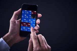 スマートフォンで株を確認する手元の写真素材 [FYI04539380]