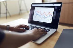 株価チャートをパソコンで確認する手元の写真素材 [FYI04539382]