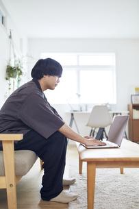 自宅でパソコンを操作する男性の写真素材 [FYI04539384]