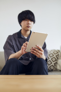 ソファでタブレットを操作する男性の写真素材 [FYI04539385]
