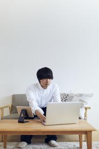 リビングでパソコンとタブレットを操作する男性の写真素材 [FYI04539386]