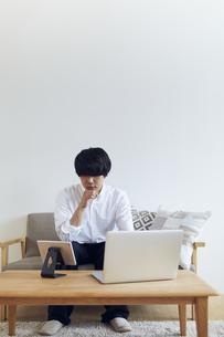 リビングでパソコンとタブレットを前に悩む男性の写真素材 [FYI04539387]