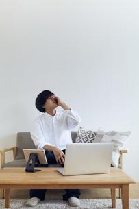 リビングでパソコンとタブレットを前に頭を抱える男性の写真素材 [FYI04539390]
