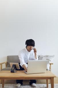 リビングでインカムをつけてパソコンとタブレットを操作する男性の写真素材 [FYI04539392]