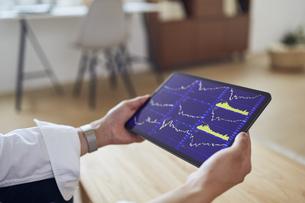 タブレットで株価チャートを確認する手元の写真素材 [FYI04539400]