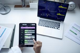 デスクでパソコンを確認しながらタブレットで株を発注する男性の写真素材 [FYI04539409]