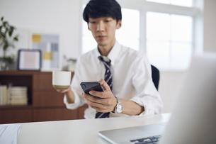 自宅のデスクでスマートフォンを操作するサラリーマンの写真素材 [FYI04539421]