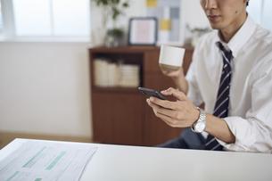 自宅のデスクでスマートフォンを操作するサラリーマンの写真素材 [FYI04539422]
