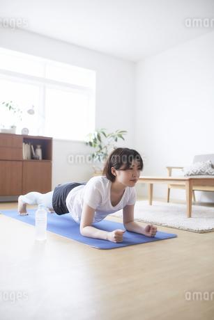 室内の床でトレーニングする女性の写真素材 [FYI04539683]