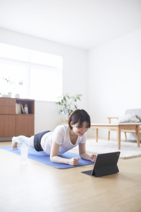 室内の床でノートパソコンを見ながらトレーニングする女性の写真素材 [FYI04539686]