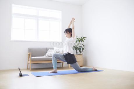 室内の床でノートパソコンを見ながらヨガのポーズをする女性の写真素材 [FYI04539690]