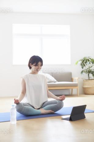 室内で床でノートバソコンを見ながらヨガのポーズをする女性の写真素材 [FYI04539694]