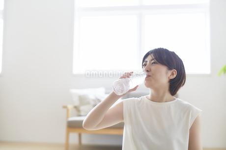 室内でペットボトルで水分補給する女性の写真素材 [FYI04539697]