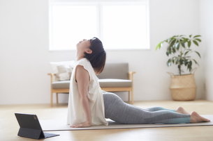 室内の床でノートパソコンを見ながらヨガのポーズをとる女性の写真素材 [FYI04539702]