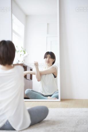 鏡に向かってストレッチをする女性の写真素材 [FYI04539705]