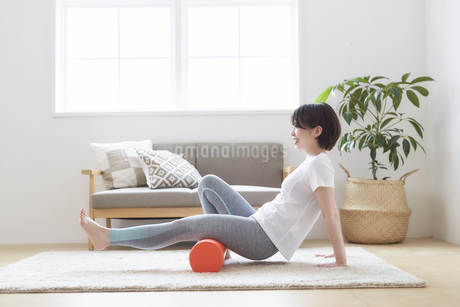 室内の床でストレッチポールを使ってストレッスル女性の写真素材 [FYI04539708]