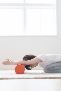 室内の床でストレッチポールを使って腕のストレッスル女性の写真素材 [FYI04539711]