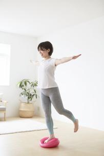 室内でバランスディスクを使ってトレーニングする女性の写真素材 [FYI04539712]