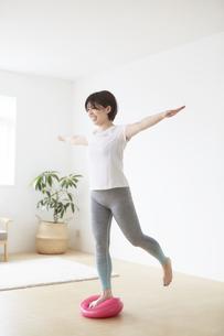 室内でバランスディスクを使ってトレーニングする女性の写真素材 [FYI04539713]