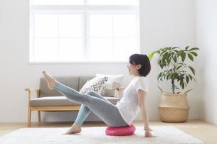 室内でバランスディスクを使ってトレーニングする女性の写真素材 [FYI04539714]