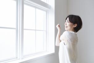 窓へで外を見ながら腕のストレッチをする女性の写真素材 [FYI04539717]