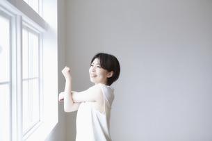 窓へで外を見ながら腕のストレッチをする女性の写真素材 [FYI04539718]
