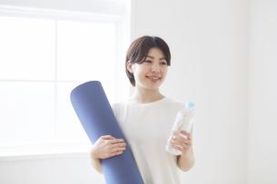 室内でヨガマットとペットボトルを手に持つ女性の写真素材 [FYI04539719]