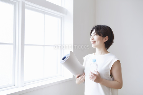 窓辺でヨガマットとペットボトルを持つ女性の写真素材 [FYI04539720]