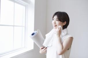 窓辺でヨガマットを持ちながら汗をタオルで拭く女性の写真素材 [FYI04539721]