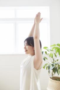 室内で腕をのばしストレッチする女性の写真素材 [FYI04539722]