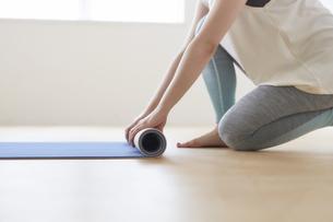 床でヨガマットを丸めている女性の手元の写真素材 [FYI04539723]