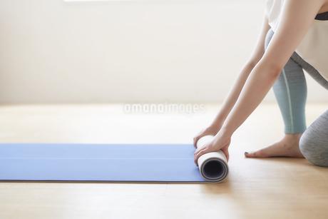 床でヨガマットを丸めている女性の手元の写真素材 [FYI04539724]