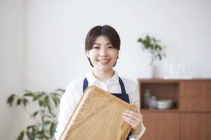 室内でトレーを持って立つ笑顔の女性の写真素材 [FYI04539725]