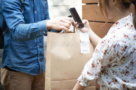 デリバリーの商品を受け取っている女性の写真素材 [FYI04540085]