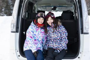 車のトランクに座り微笑むウィンターウェアの女性の写真素材 [FYI04540104]