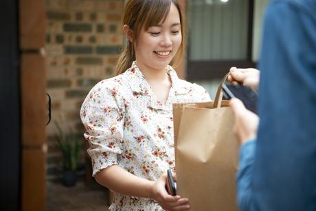 デリバリーの商品を笑顔で受け取っている女性の写真素材 [FYI04540151]