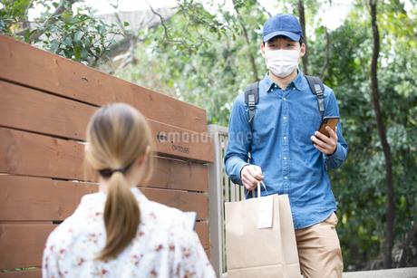 マスクをしたデリバリーの配達員と女性の写真素材 [FYI04540152]