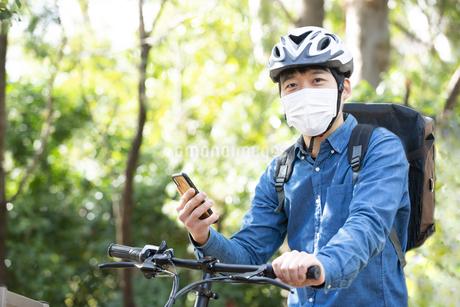 スマホを持ってバイクにまたがっている配達員の写真素材 [FYI04540183]