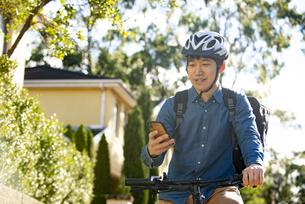 自転車に乗ってスマホを見ている配達員の写真素材 [FYI04540191]