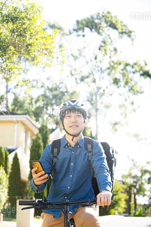 スマホを持って自転車にまたがっている配達員男性の写真素材 [FYI04540197]