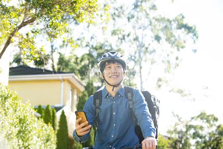 スマホを持って自転車にまたがっている配達員男性の写真素材 [FYI04540200]
