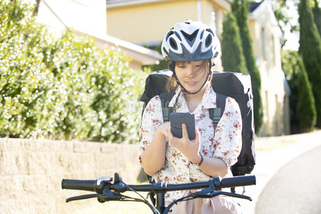 自転車にまたがってスマホを触っている配達員女性の写真素材 [FYI04540203]